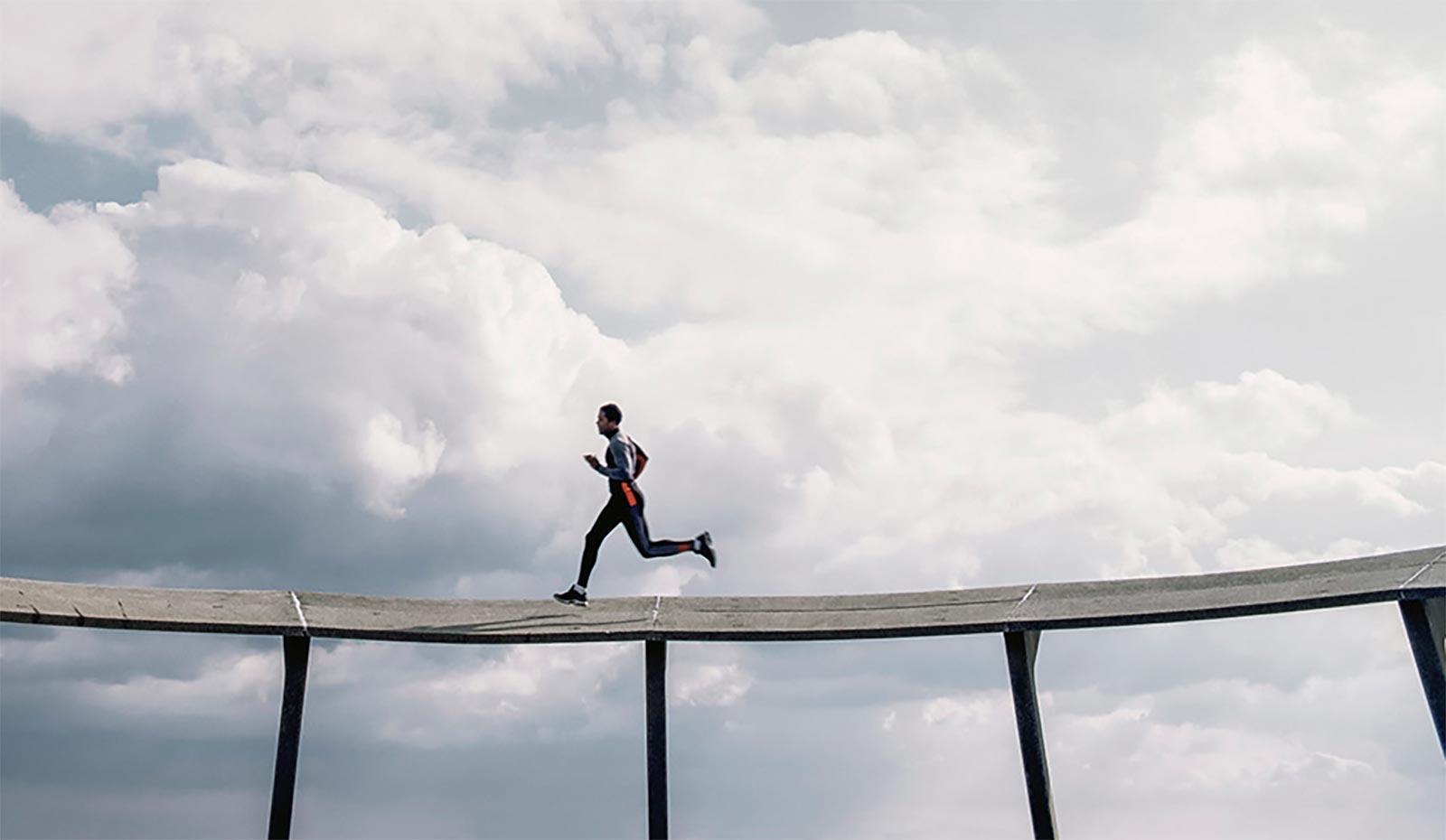 Athlete running on sky bridge