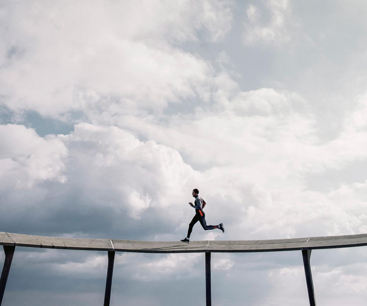 Athletic man running on sky bridge