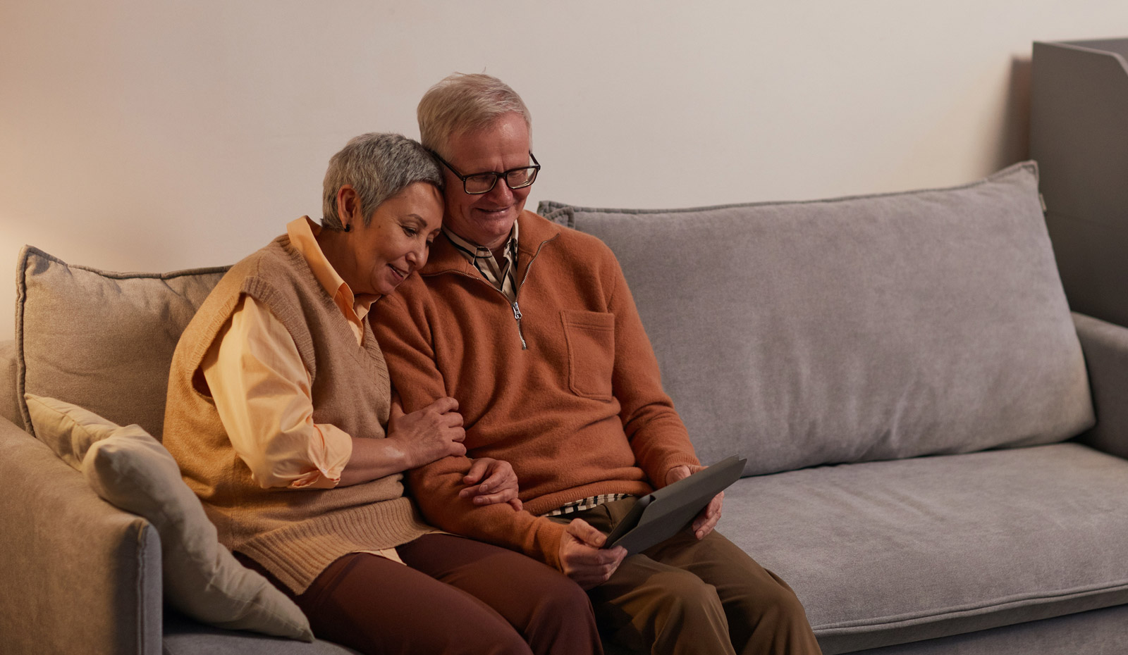 Elderly couple on couch using tablet computer