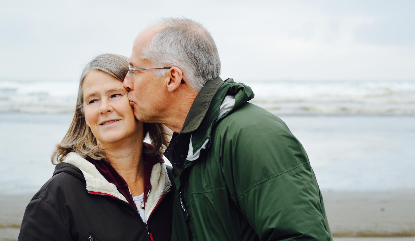 Middle aged couple kissing on beach