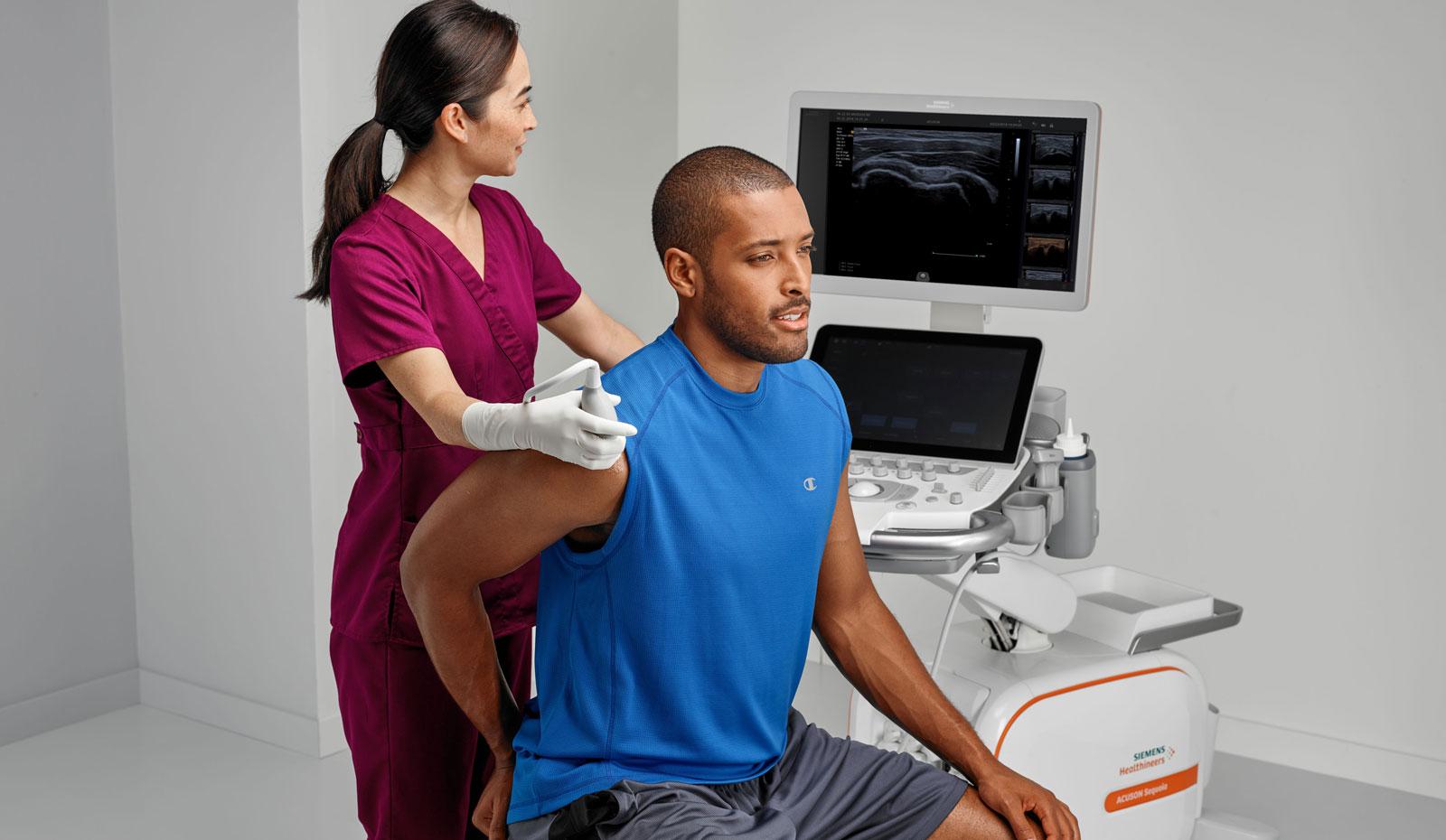Sonographer using ultrasound equipment on patient's shoulder